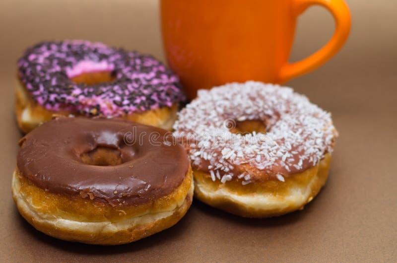 Wyśmienicie donuts z czekoladą, koksem i menchiami glazurującymi, z pomarańczową filiżanką czekolada w drewnianym tle zdjęcie royalty free