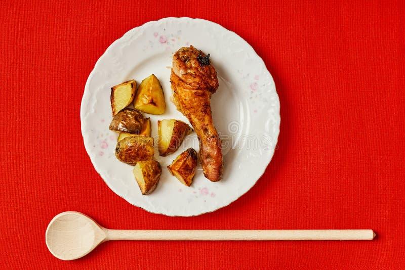 Wyśmienicie gość restauracji z kurczak nogami i piec grulami na czerwień stole zdjęcie royalty free