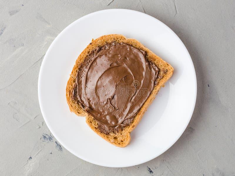 Wyśmienicie grzanka z czekoladową pastą na białym talerzu, zbliżenie, odgórny widok obrazy royalty free