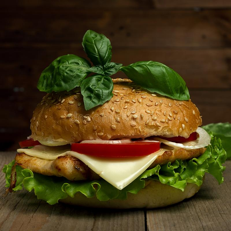 Wyśmienicie hamburger z serem, pomidorami i basilem na drewnianym tle, Fastfood posiłek fotografia royalty free