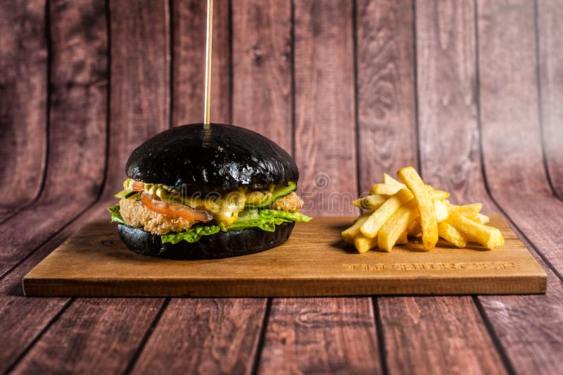Wyśmienicie hamburgery czarny ciasto z czerwieni ryba na pięknym łupku wsiadają obrazy stock