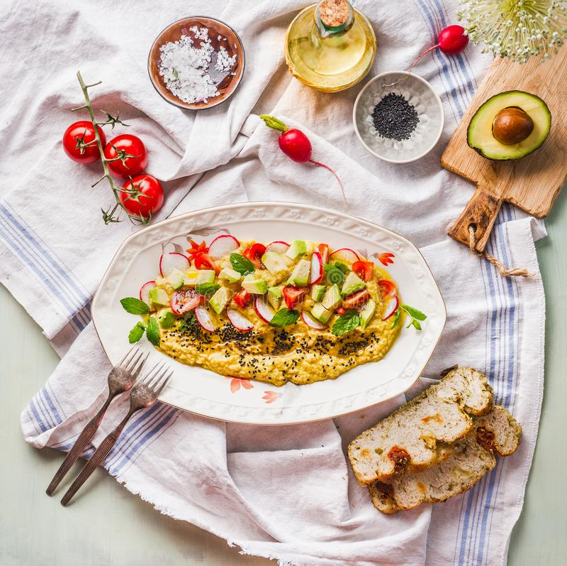 Wyśmienicie hummus talerz nakrywający z oliwą z oliwek, avocado, świeżymi warzywami i ziele, słuzyć na kuchennym stole z rozwidle fotografia royalty free