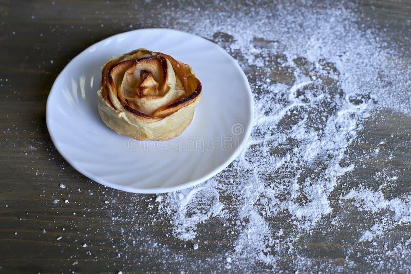 Wyśmienicie i cukierki piec róża kształtował ciasto z jabłczanym plombowaniem na bielu talerzu na drewnianym tle pudrującym z ryc zdjęcie stock