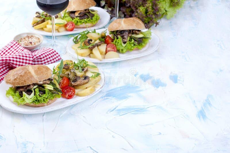 Wyśmienicie jarskie grule dla trzy i hamburgery Sałatka Lunch i wino Lekki tło i przestrzeń dla teksta linii brzegowej zielonej h fotografia royalty free