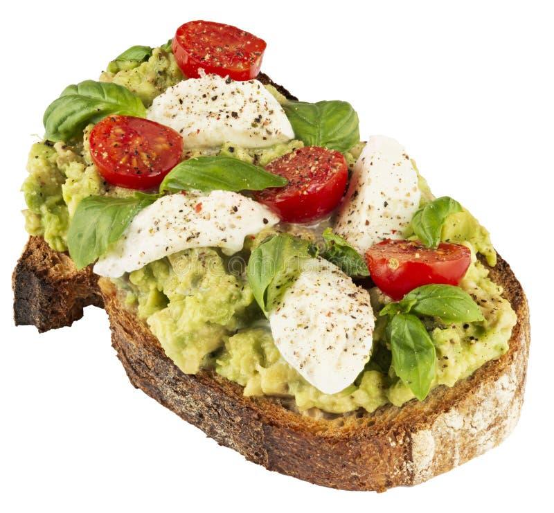 Wyśmienicie kanapka z świeżą mozzarellą, avocado i pomidorami, fotografia stock