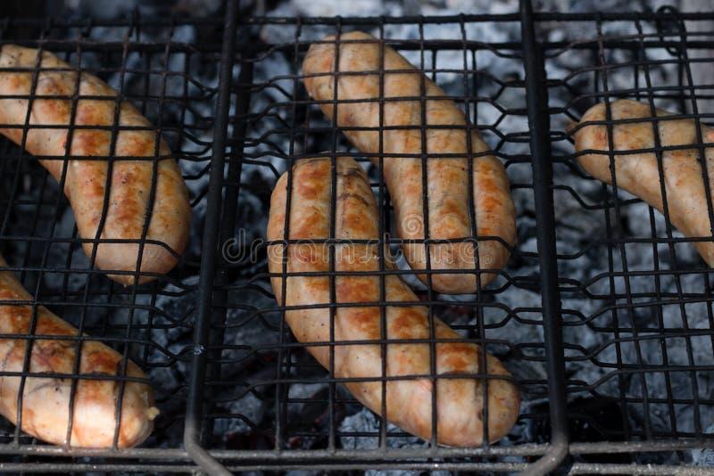Wyśmienicie mięsne kiełbasy piec na grillu na drewnianym półkowym tle fotografia royalty free