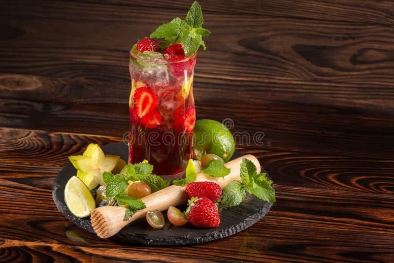 Wyśmienicie odświeżający stawberry koktajl z mennicą, lodem, wapno segmentami i kawałkami truskawka, Lato napoje kosmos kopii zdjęcia stock