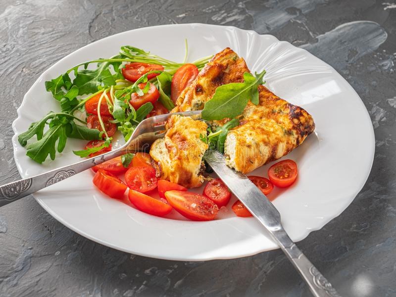 Wyśmienicie omlet z ziele i rozcięciem czereśniowi pomidory na talerzu białym cutlery i, świeży arugula fotografia royalty free
