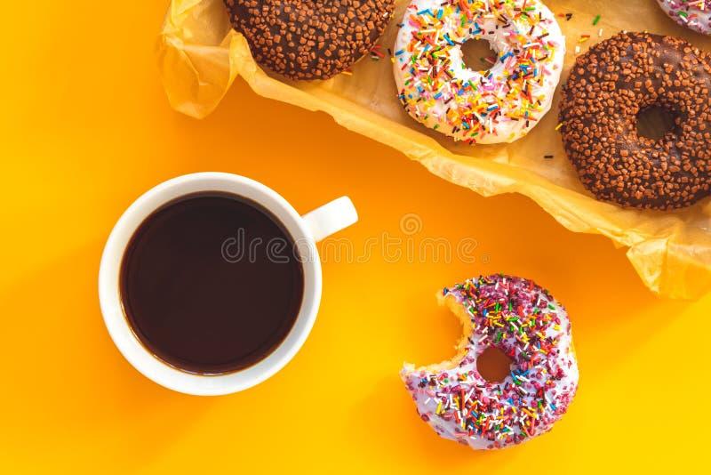 Wyśmienicie oszkleni donuts w pudełku i filiżance kawy na kolorze żółtym ukazują się zdjęcie royalty free