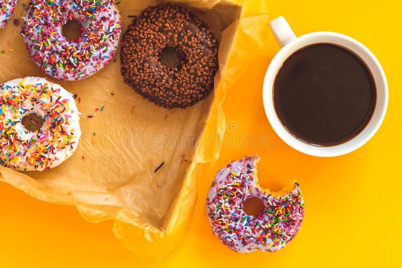 Wyśmienicie oszkleni donuts w pudełku i filiżance kawy na kolorze żółtym ukazują się fotografia stock