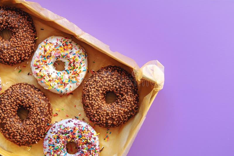 Wyśmienicie oszkleni donuts w pudełku na fiołku ukazują się zdjęcia royalty free