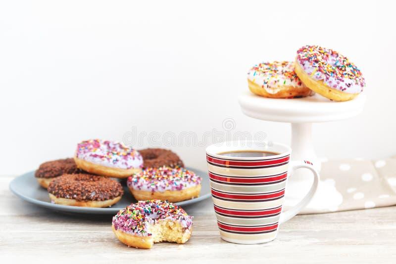 Wyśmienicie oszklona filiżanka kawy na lekkim drewnianym backgr i donuts fotografia stock