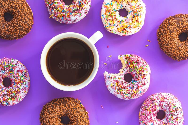 Wyśmienicie oszklony filiżanka kawy na fiołku i donuts ukazują się zdjęcie royalty free