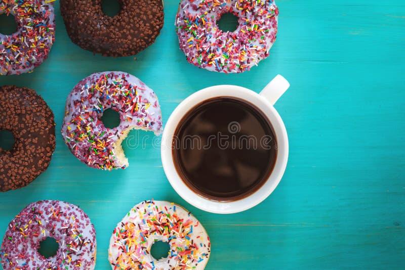 Wyśmienicie oszklony filiżanka kawy na turkusowym błękicie i donuts surfują obraz stock