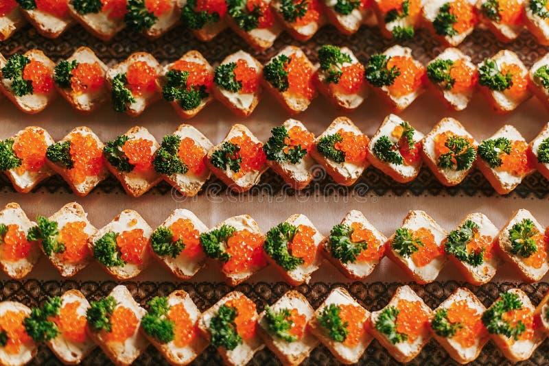 Wyśmienicie palcowy zakąska stół przy weselem Kawior na chlebowych canapes wiosłuje odgórnego widok na stole przy ślubem lub boży fotografia royalty free