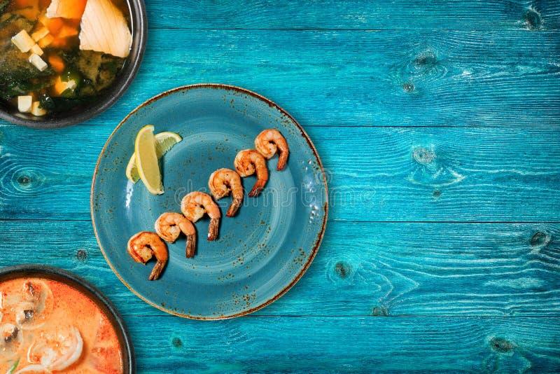 Wyśmienicie polewki na błękitnym talerzu na drewnianym stole i garnele obraz royalty free
