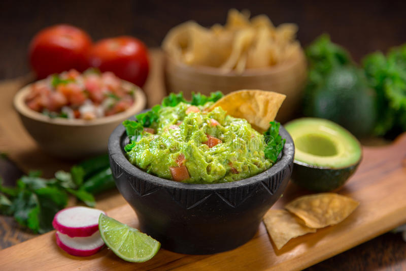 Wyśmienicie puchar Guacamole obok świeżych składników na stole z tortilla salsa i układami scalonymi zdjęcia stock