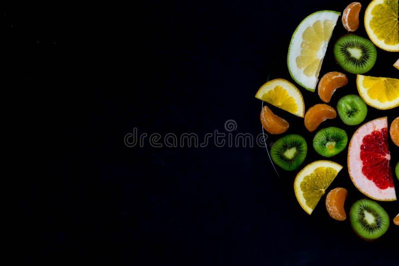 Wyśmienicie rżnięte jaskrawe słodkie acidic cytrus owoc w talerzu z krawędzią zmrok - błękitny tło z miejscem dla teksta przylepi obraz stock