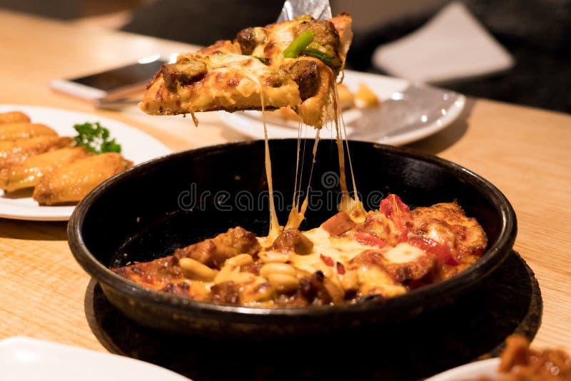 Wyśmienicie serowy kleisty plasterek podnoszący niecki pizza, tło z piec na grillu kurczakiem na drewnianym stole, zdjęcie stock