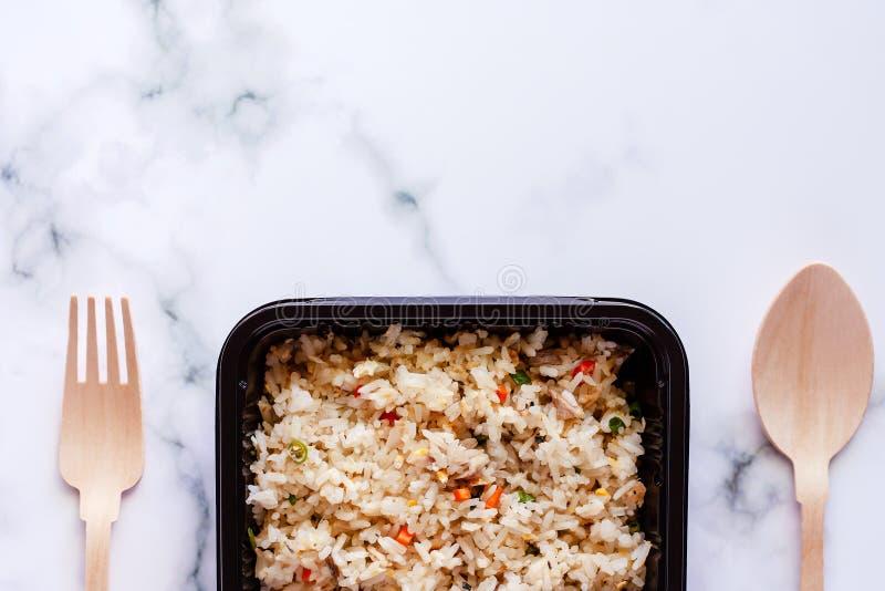 Wyśmienicie smażący ryż w lunchu pudełku z drewnianą łyżką i rozwidlenie na marmurowym tle obraz stock