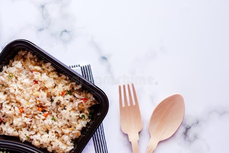 Wyśmienicie smażący ryż w lunchu pudełku z napery, drewnianą łyżką i rozwidleniem na marmurowym tle, zdjęcie royalty free