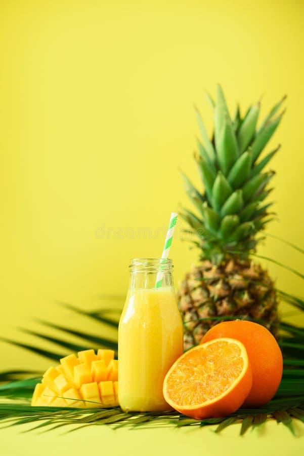 Wyśmienicie soczysty smoothie z pomarańczową owoc, mango, ananas na żółtym tle kosmos kopii Wystrzał sztuki projekt, kreatywnie zdjęcia royalty free