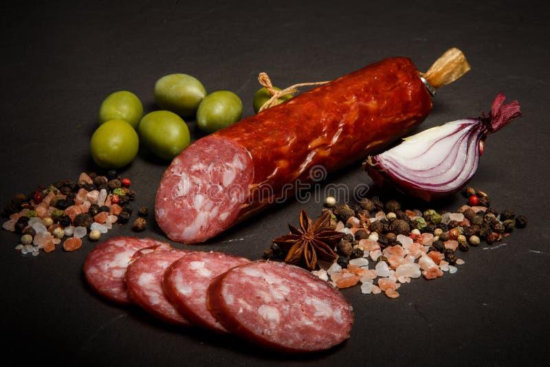 wyśmienicie suszy leczącą uwędzoną salami kiełbasę z cebulą i oliwkami fotografia stock