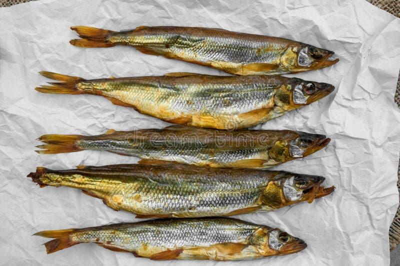 Wyśmienicie uwędzona ryba wytapia Osmerus lying on the beach na barwiącym papierze na drewnianym tle fotografia royalty free