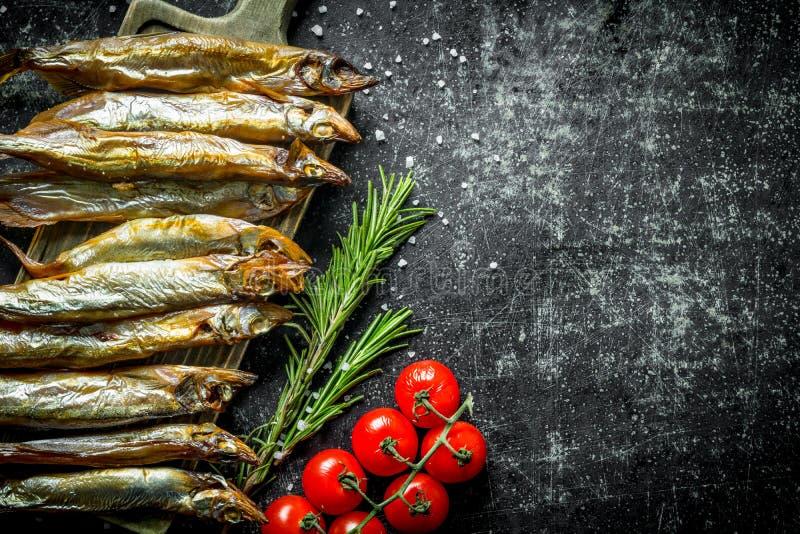Wyśmienicie uwędzona ryba z rozmarynami i pomidorami na gałąź obrazy royalty free