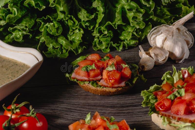 Wyśmienicie Włoski antipasti bruschetta z siekającym pomidorem, mięsnym łbem, kumberlandem, kremowym serem i sałatka liść zdjęcia royalty free
