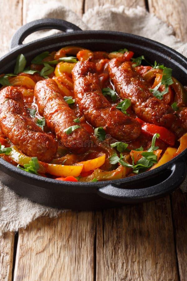 Wyśmienicie Włoskie kiełbasy piec na grillu z dzwonkowymi pieprzami, cebulami i pomidorami wewnątrz w górę smaży niecki, pionowo zdjęcie stock