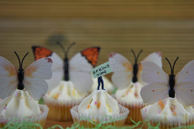 Wyśmienicie wiosen babeczki nakrywać z dekoracjami motyl kształtują na nieociosanym drewnianym tle obraz stock