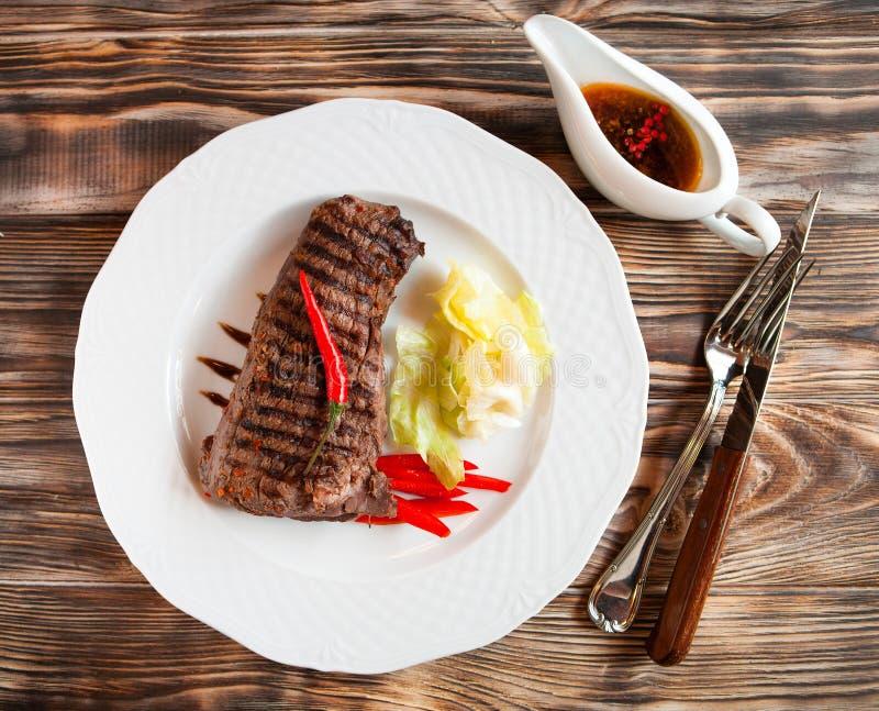 Wyśmienicie wołowiien steakes z chili na bielu talerzu na drewnianym plecy zdjęcie royalty free