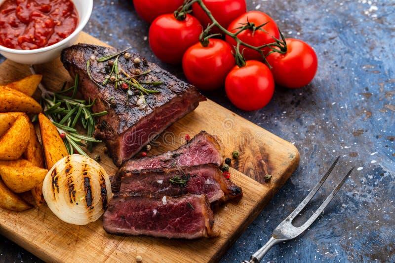Wyśmienicie wołowina stek na drewnianej tnącej desce Pokrojona piec na grillu pszczoła obrazy stock