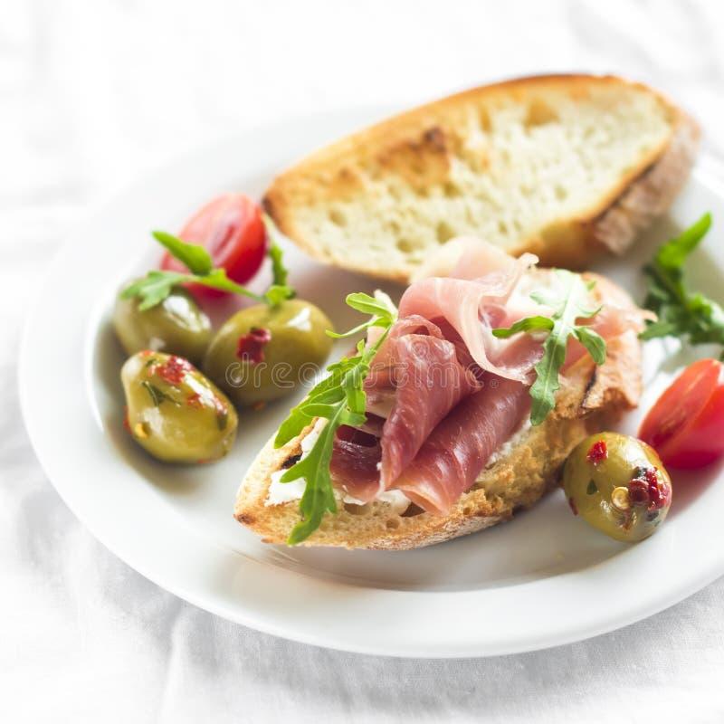 Wyśmienicie zakąska wino - grzanka z baleronem, oliwkami i czereśniowymi pomidorami, obrazy stock