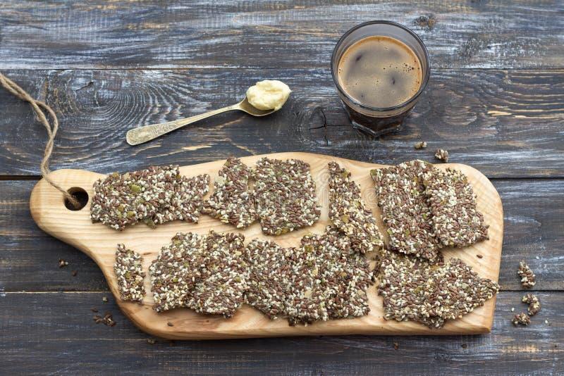 Wyśmienicie zdrowego multigrain bezpłatna krakersów, ketogenic i keto kawa w szkle z łyżką masło, obrazy stock