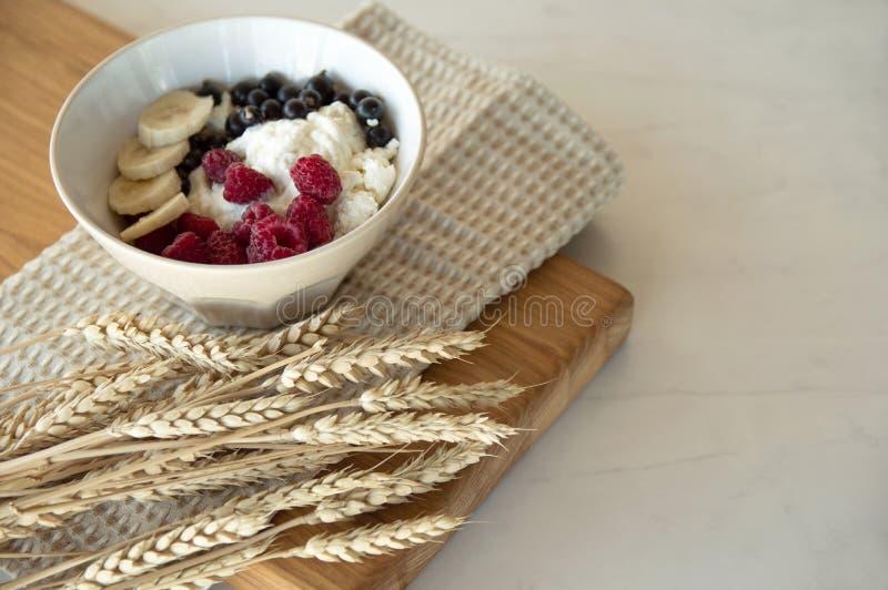 Wyśmienicie zdrowy śniadanie chałupa ser z jagodami Biały talerz z chałupa serem i jagoda stojaki na drewnianej desce obrazy stock