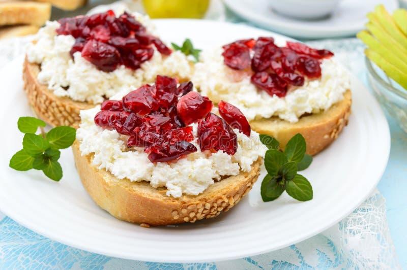 Wyśmienicie zdrowy śniadanie: kanapki z feta chałupy serem, wysuszeni cranberries, bonkrety, mennica zdjęcia royalty free