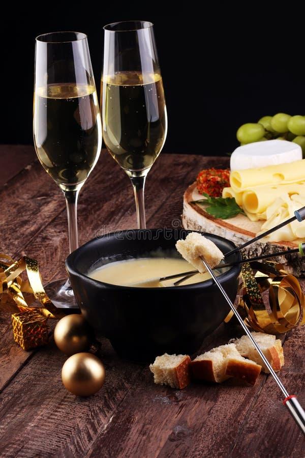 Wyśmienity Szwajcarski fondue gość restauracji na zima wieczór z asortowanymi serami na desce przy gorący garnek serowy fondue z  zdjęcie stock
