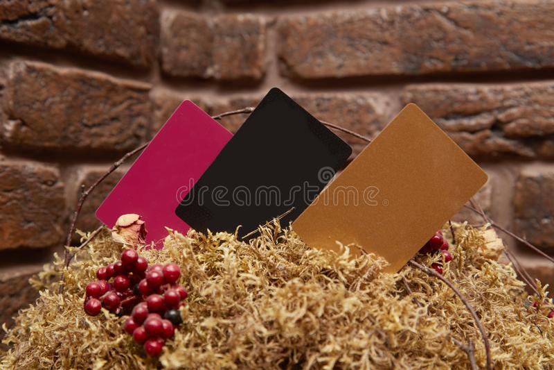 Wyśmiewa up czarne czerwone i złociste wizytówki na textured ceglanym tle obraz stock