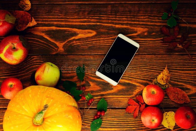 Wyśmiewa up, smartphone z czerwonymi jabłkami z żółtymi i czerwonymi jesień liśćmi na drewnianym oczyszczonym tle obraz royalty free