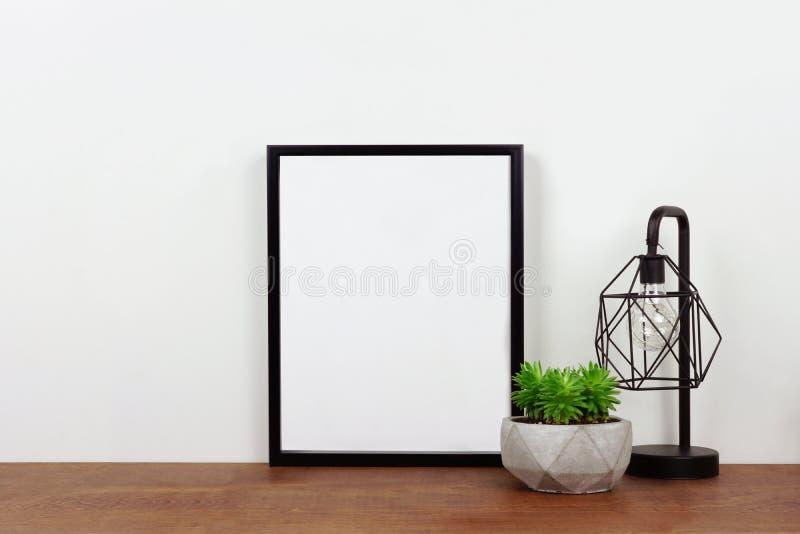 Wyśmiewa w górę czerni ramy przeciw biel ścianie z rośliną i lampą na drewnianej półce zdjęcia stock