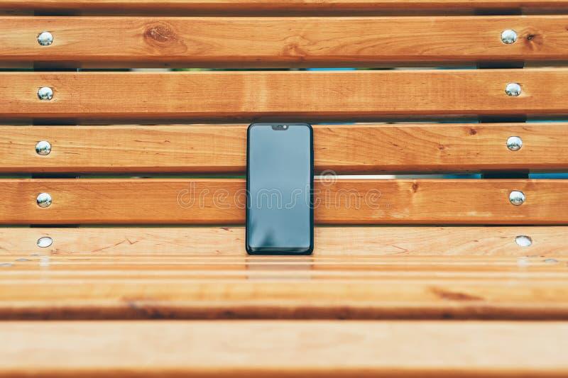 Wyśmiewa W górę smartphone, przeciw tłu drewniana ławka zdjęcie stock