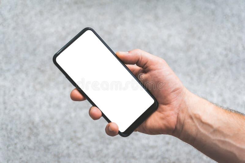 Wyśmiewa w górę smartphone w ręce, na tle betonowe płytki zdjęcie royalty free