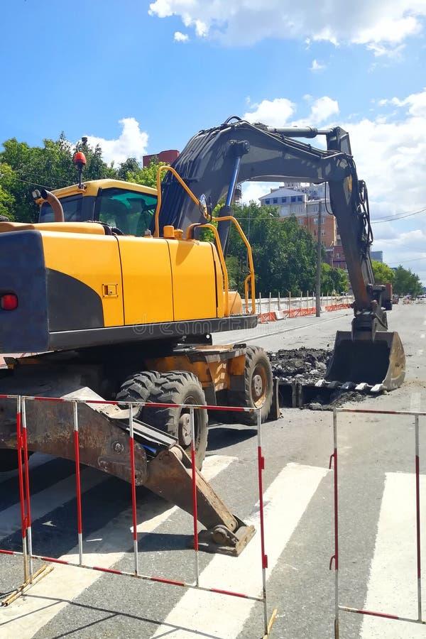 Wy?ledzony ekskawator na ulicznej asfaltowej drogi naprawie zdjęcie stock