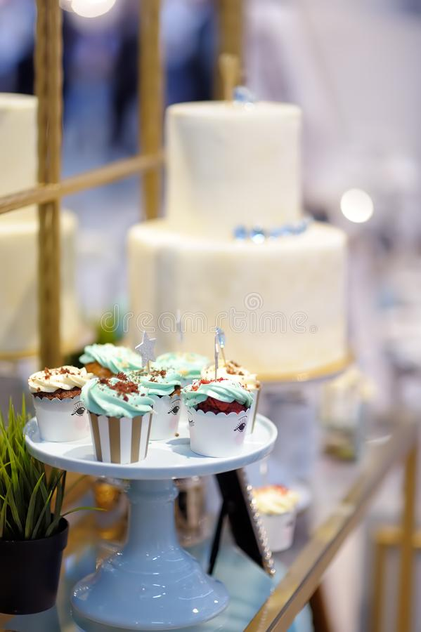 Wy?mienicie kolorowe ?lubne babeczki z kwiatem, gwiazdy i pi?kny oszklony tort Elegancki cukierki st?? zdjęcie stock