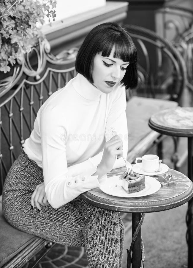 Wy?mienicie smakosza tort Kobiety atrakcyjna brunetka je smakosz kawiarni tarasu tortowego t?o Gastronomical przyjemno?? fotografia stock