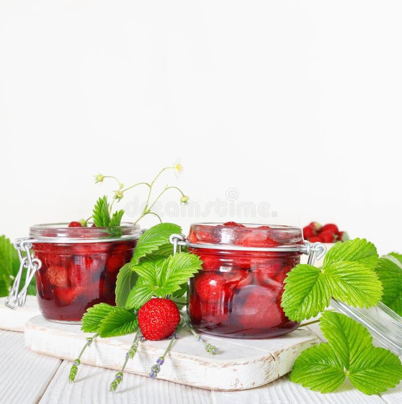 Wy?mienicie truskawkowy d?em w tradycyjnym szklanym s?oju na bia?ym drewnianym tle fotografia stock