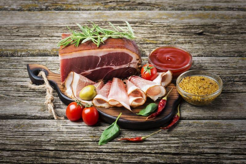 Wy?mienicie uw?dzony baleron na drewnianym stole z rozmarynami, pieprzem i czere?niowymi pomidorami, Odg?rny widok zdjęcie stock