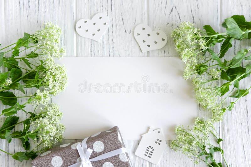 Wy?miewa w g?r? pustego papieru, poczty koperty na ciemnym drewnianym tle z naturalnymi kwiatami bia?y kolor i motyli, zdjęcia royalty free